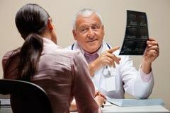 显示X-射线的放射学家对患者 免版税库存图片
