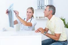 显示X-射线的医生对她的患者 免版税库存照片