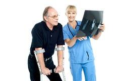 显示X-射线页的外科医生对她的患者 免版税库存照片