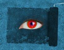 显露一只红色眼睛的漆滚筒 库存照片