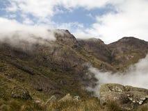 晃动一座山的面孔与有些树、灌木和云彩的 免版税库存图片