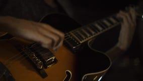 晃动使用在吉他的音乐家在音乐音乐会 关闭吉他演奏员戏剧音乐的手到在阶段的吉他 股票视频