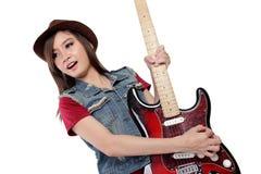 晃动在她的吉他的美丽的亚裔女孩,在白色背景 免版税库存照片