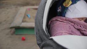 晃动婴儿车特写镜头的母亲 在模糊的背景的沙盒 影视素材