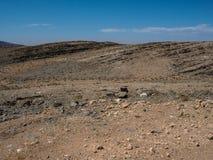 晃动山纳米比亚沙漠干多灰尘的风景有分裂的页岩、其他石头和沙漠植物的 库存图片