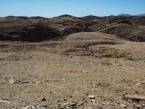晃动山纹理衬里纳米比亚沙漠独特的地理风景背景与分裂的石地面和沙漠植物的 图库摄影