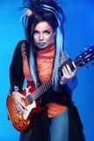 晃动摆在与电吉他的女孩演奏难石  图库摄影