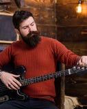 晃动有摆在与仪器的残酷看起来的音乐家 调整电吉他的有胡子的人 有时髦的胡子的人和 免版税库存图片