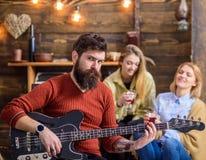 晃动有长的弹吉他的胡子和被刺字的胳膊的音乐家 有看照相机的严厉的眼睛的有胡子的人 吉他弹奏者 库存照片