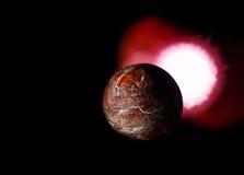 晃动行星和红色太阳在黑背景 免版税库存图片