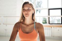 晒斑运动的女服无线耳机画象和体育在晴朗的健身房佩带 库存照片