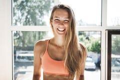 晒斑适合妇女佩带的sportwear画象在晴朗的白色健身房的 免版税图库摄影