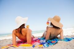 晒日光浴回到观点的美丽的妇女,当啜饮在海滩时的鸡尾酒 库存图片