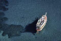 晒日光浴在一条小船的马尔马里斯港海岸线在透明的大海 库存照片