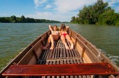 晒日光浴在小船的逗人喜爱的十几岁的女孩 图库摄影