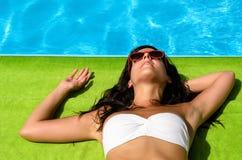 晒日光浴在游泳池边的浅黑肤色的男人 免版税库存照片