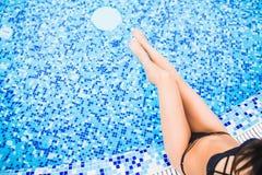 晒日光浴在游泳池附近的美好的妇女腿 夏天职业 免版税库存图片