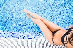 晒日光浴在游泳池附近的美好的妇女腿 夏天职业 库存图片