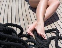 晒日光浴在船的甲板 关闭在木地板上的女性脚 免版税库存照片