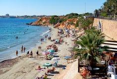 晒日光浴在蓬塔Prima多岩石的海滩的人们  西班牙 库存照片