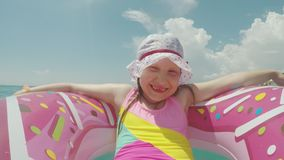 晒日光浴滑稽的女孩一个桃红色可膨胀的圆环的和一滑稽的儿童` s panamka的在阳光下,滚动在海挥动 股票视频