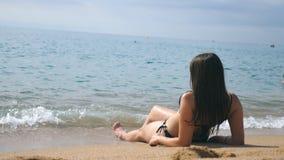 晒日光浴的比基尼泳装的女孩说谎在海海滩和 放松在海洋岸的美丽的无法认出的妇女在期间 股票视频