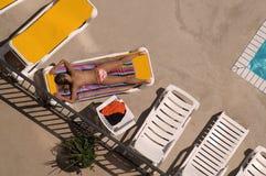 晒日光浴的游泳池边 免版税图库摄影