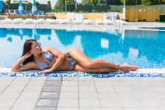 晒日光浴美丽的性感的女孩说谎在游泳池边缘 夏天职业 免版税库存照片