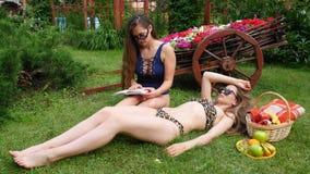 晒日光浴俏丽的女孩和阅读书 股票录像