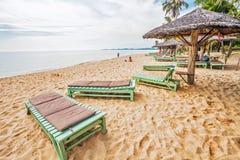 晒日光浴在一个热带海滩的沙子的游人 免版税库存图片