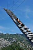 晒日光浴在一架木梯子的性感的妇女 免版税库存图片