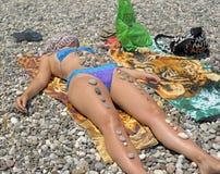 晒日光浴在与小卵石的海滩的妇女 库存图片