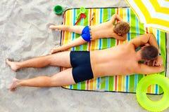 晒日光浴在五颜六色的毯子的父亲和儿子 免版税库存图片