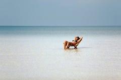晒日光浴在华美的水晶水,柬埔寨中的可爱的妇女 图库摄影