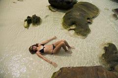 晒日光浴在华美的水晶水,柬埔寨中的可爱的妇女 免版税图库摄影