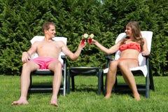 晒日光浴在后院和敬酒的夫妇 库存照片