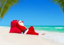 晒日光浴在圣诞节礼物大袋的圣诞老人在海洋棕榈bea 库存图片