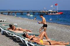晒日光浴在安塔利亚有卵石花纹的海滩胜地的男孩和女孩  库存照片