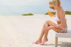 晒日光浴在比基尼泳装和应用遮光剂的妇女 免版税图库摄影