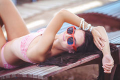晒日光浴在比基尼泳装的妇女在热带旅行手段。说谎在太阳懒人的美丽的少妇在水池附近。 库存图片