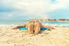 晒日光浴在沙子的妇女 库存照片