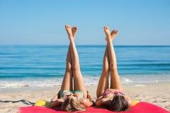 晒日光浴在海的女孩 免版税库存图片