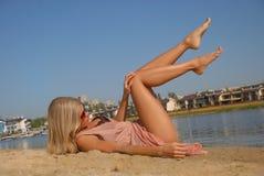 晒日光浴在海边的年轻人相当白肤金发的妇女 免版税图库摄影