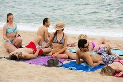 晒日光浴在海滩的人们 免版税库存照片