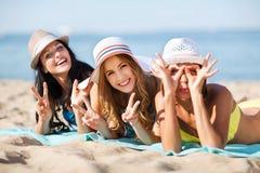 晒日光浴在海滩的女孩 免版税库存图片