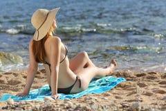 晒日光浴在海滩的妇女在夏天 免版税库存图片
