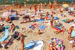 晒日光浴在海滩的很多人民 免版税库存图片