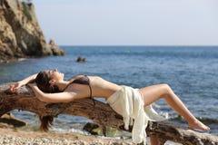 晒日光浴在海滩的日光浴者美丽的妇女 免版税库存图片