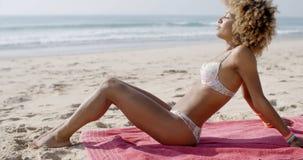 晒日光浴在海滩的美丽的妇女 免版税库存照片