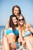 晒日光浴在海滩睡椅的女孩 免版税库存图片